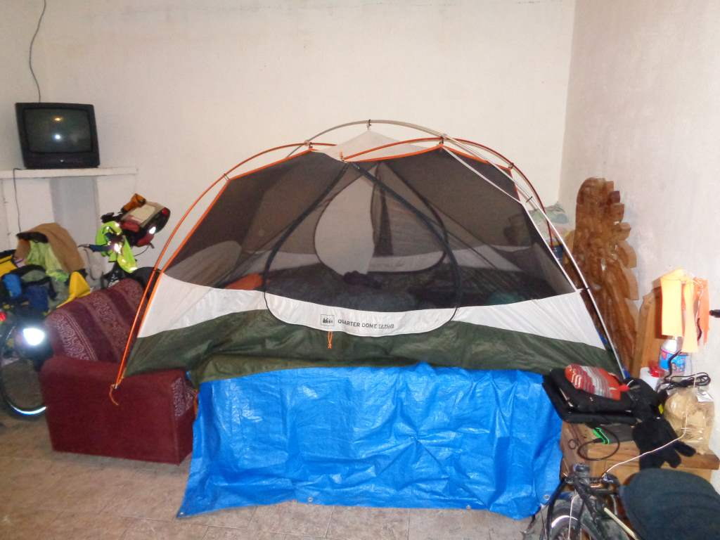 This hotel was so cheap ($8) that they forgot to put the right size door in the frame.  As a result, the mosquitoes snuck in and forced us to set up the tent on top of the bed!