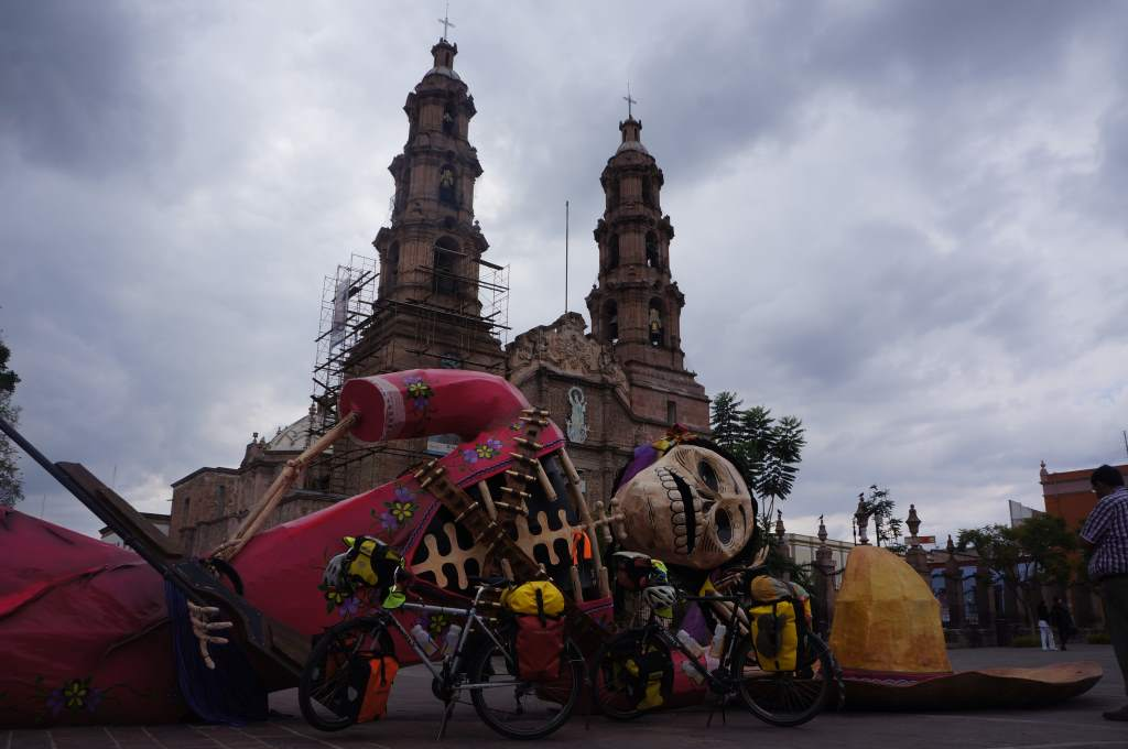 Our bikes in the main square of Aguascalientes with a left-over sculpture from Day of the Dead.