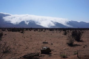 Tendrils of fog creeping over the mountains into the desert.